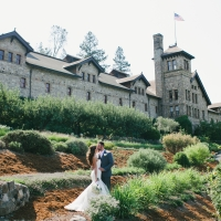 Wedding couple in front of the historic stone building of The Culinary Institute of America at Greystone in St. Helena, CA.