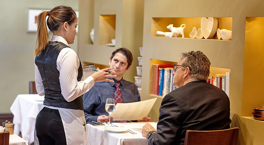 Server helping guests at the Gatehouse Restaurant, St. Helena, CA, located at the CIA at Greystone.