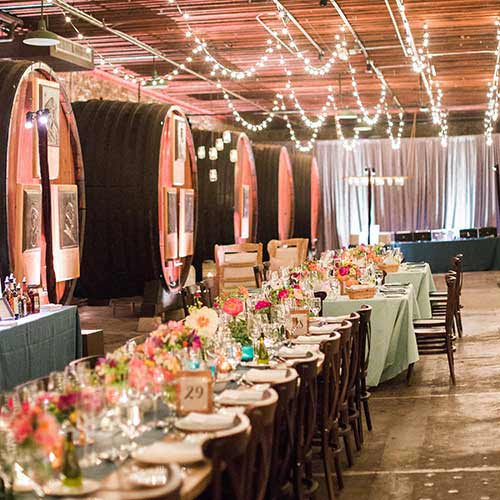 Wedding tables set up in the Barrel Room, on the campus of The Culinary Institute of America at Greystone in St. Helena, CA. The Barrel Room features 2,000-gallon Redwood wine barrels, exposed stone walls, and wooden beams throughout.