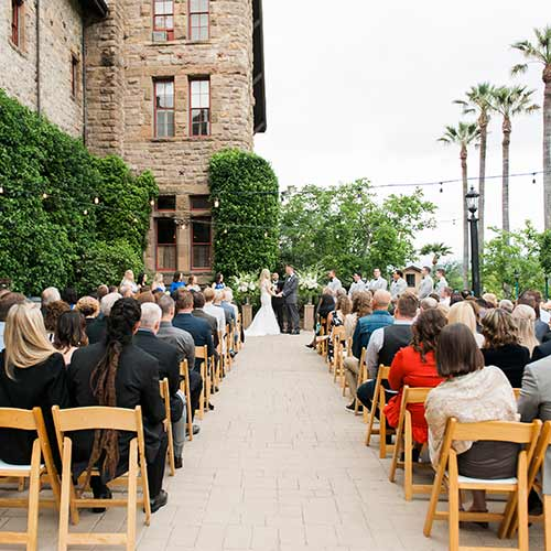 Couple getting married on the Herb Terrace at The Culinary Institute of America at Greystone in St. Helena, CA. The Herb Terrace has stunning views of the Napa Valley and is surrounded by the ivy-covered stone walls of the landmark Greystone building, flowering beds and herb gardens.