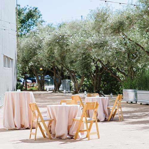 Jackson Family Wines Amphitheater Patio, an outdoor patio surrounded by olive trees, perfect for a unique dining experience or reception at the CIA at Copia in Napa, CA.