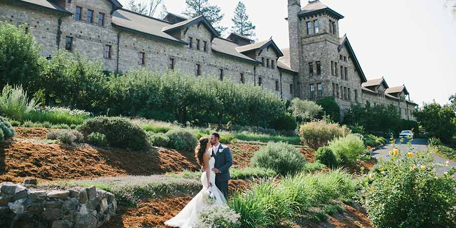 A wedding couple in front of the Culinary Institute of America at Greystone in the Napa Valley of California.